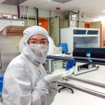 Gowned woman points to wafers in nanofabrication cleanroom